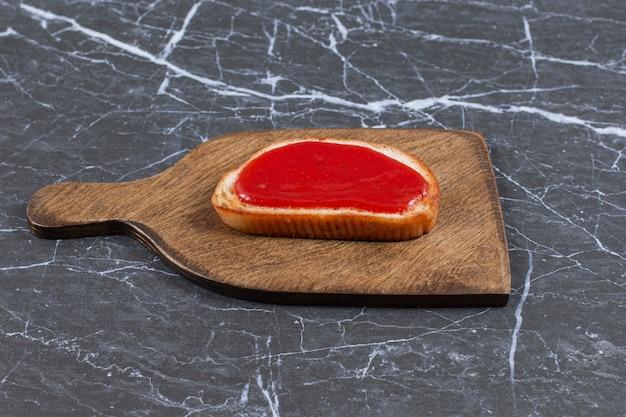 Ząbkowany dżem truskawkowy na chlebie na desce, na marmurowej powierzchni