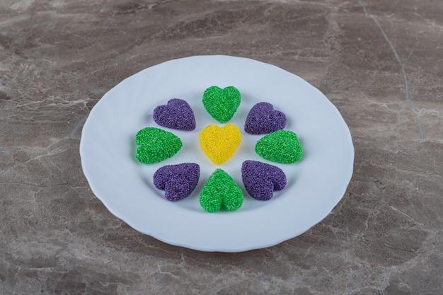 Ząbkowate ciastko na talerzu, na marmurowej powierzchni