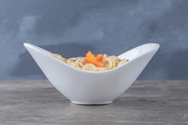 Ząbkujący makaron farfalle z pikantnym sosem pomidorowym w misce, na marmurze.