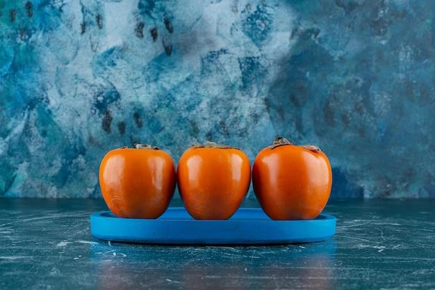 Ząbkujący owoc persimmon na drewnianym talerzu, na marmurowym stole.