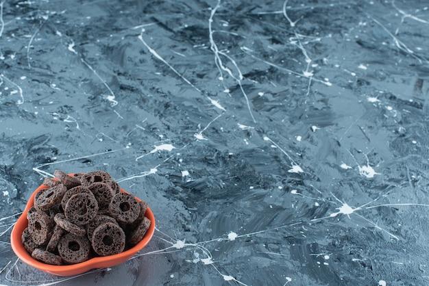 Ząbkujący pierścionek kukurydziany w czekoladzie w misce, na marmurowym stole.