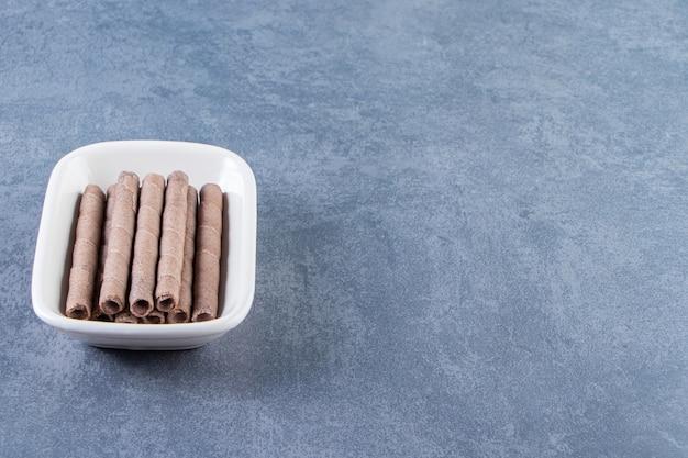 Ząbkujący wafelek czekoladowy w misce na marmurowej powierzchni