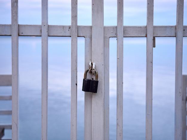 Zablokuj metalową białą barierkę na tle morza