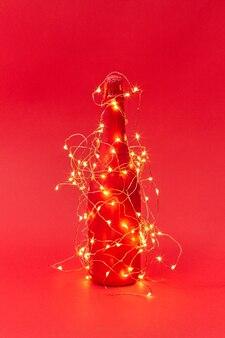 Zabłysnął sznur lampek choinkowych na kreatywnej malowanej butelce wina na czerwonym tle z miejsca na kopię. karta z gratulacjami noworocznymi.