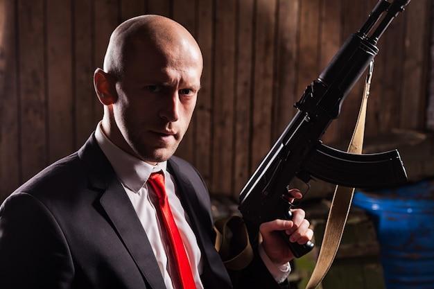 Zabójca kontraktowy trzymający w ręku karabin maszynowy. tajny agent gotowy do misji.