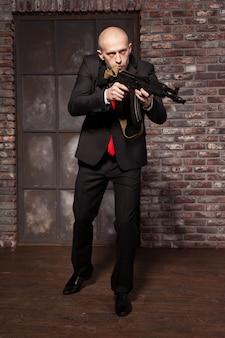 Zabójca w garniturze i czerwonym krawacie trzyma karabin maszynowy
