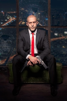 Zabójca w garniturze i czerwonym krawacie, trzymając w ręku pistolet