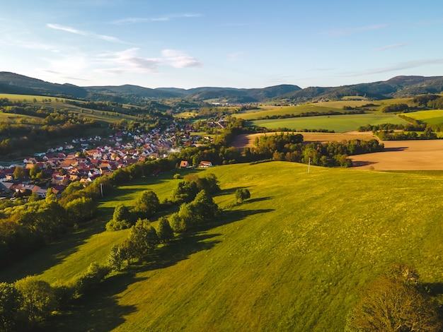 Zabudowania wsi otoczone trawą i drzewami