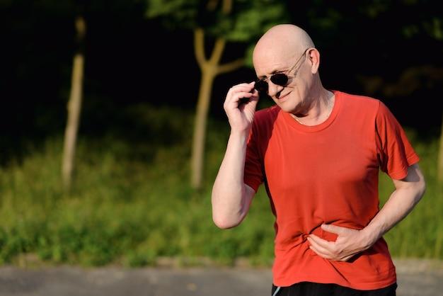 Zaburzenia żołądka, starzec trzyma ręce na brzuchu, opieka zdrowotna i koncepcja medyczna