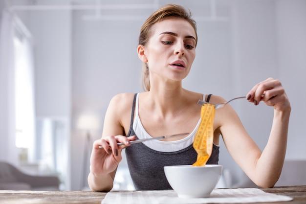 Zaburzenie psychiczne. bezczelna kobieta z niedowagą siedząca przy stole podczas posiłku