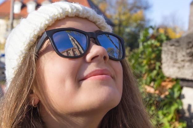 Zabytki starego miasta odbijają się w okularach na twarzy młodej uśmiechniętej kobiety