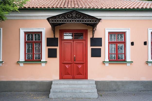 Zabytkowa architektura budynku klasycznej elewacji z czerwonymi drzwiami