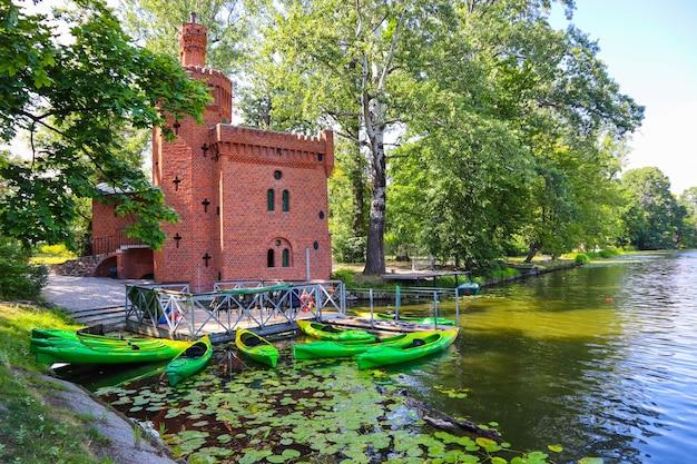 Zabytkowa przepompownia wody i łodzie na jeziorze w królewskim parku wilanowskim w warszawie. sierpień 2019