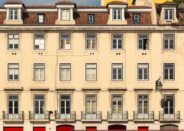 Zabytkowa ściana budynku z oknami i balkonami w tle