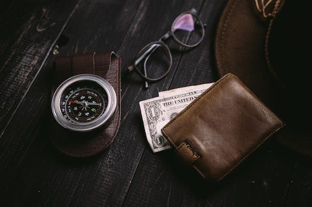 Zabytkowe banknoty na drewnianej desce ze starym zabytkowym kompasem
