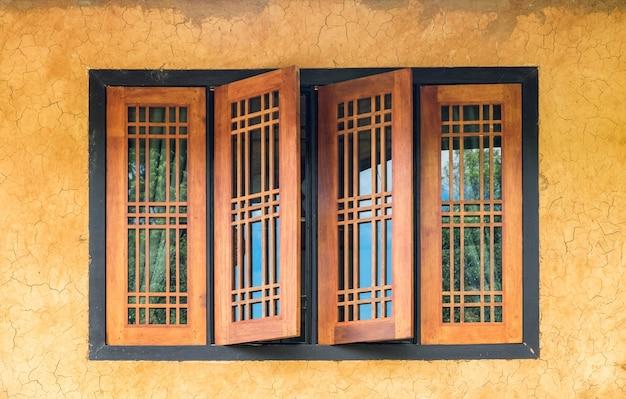 Zabytkowe drewniane okno na żółtej ścianie pęknięć