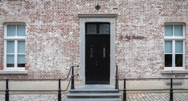Zabytkowe drzwi i okno na fasadzie starej angielskiej kamiennej chaty.