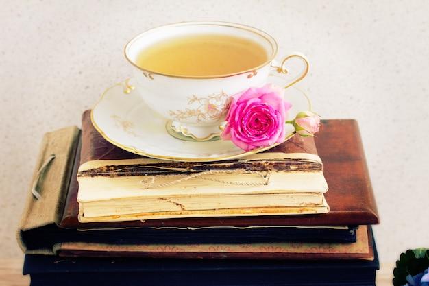 Zabytkowe książki, antyczna filiżanka herbaty i kwiat róży