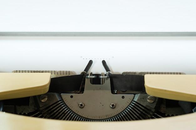 Zabytkowe maszyny do pisania z białą kartką papieru.