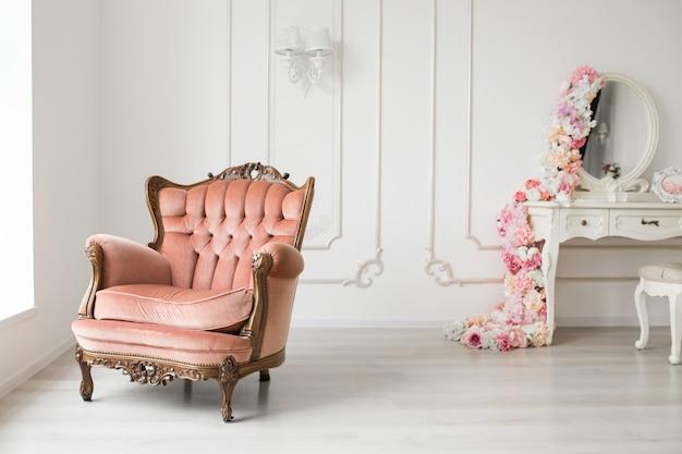 Zabytkowy fotel i antyczna biała komoda w białym pokoju.