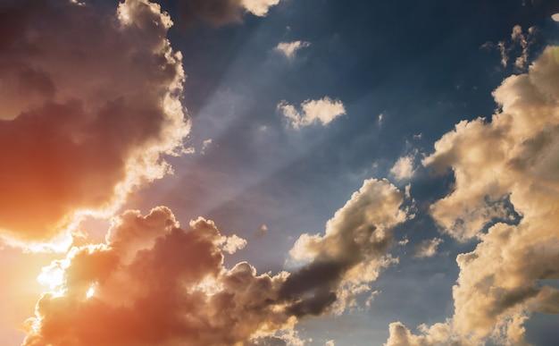 Zachmurzone niebo i jasny wschód słońca nad horyzontem.