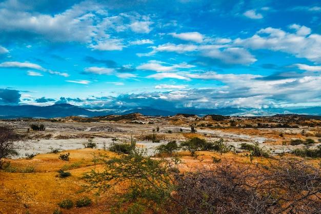 Zachmurzone niebo nad doliną z dzikimi roślinami na pustyni tatacoa w kolumbii