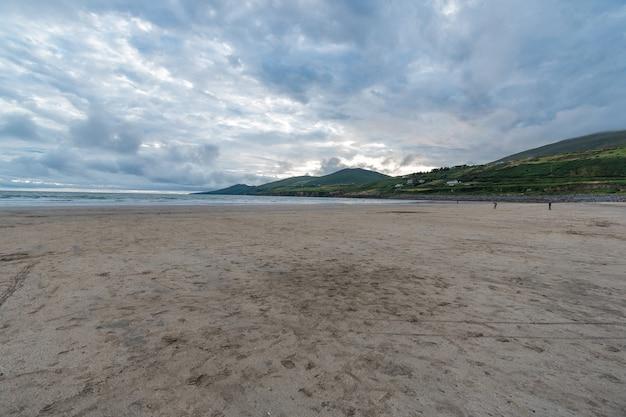 Zachmurzone niebo nad piaskami plaży z odpływem. mauntains w oddali.
