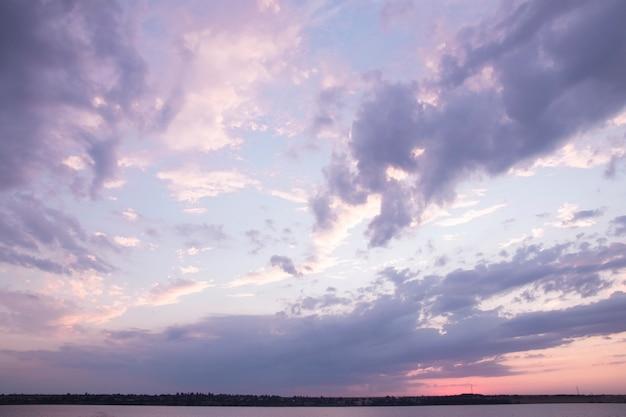 Zachmurzone niebo z fioletowymi i różowymi chmurami nad rzeką o zachodzie słońca