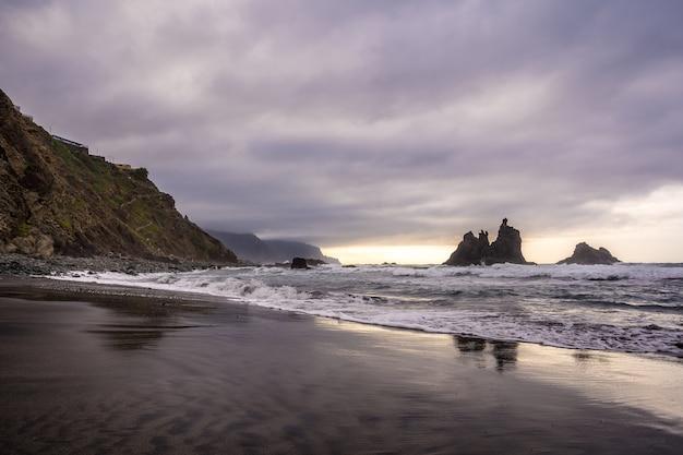 Zachmurzony zachód słońca na plaży benijo na północy teneryfy w hiszpanii