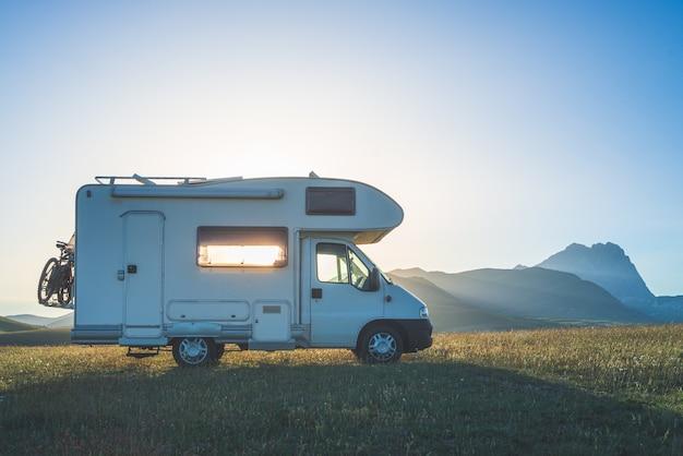 Zachód słońca dramatyczne niebo nad kamperem w wyżynach campo imperatore, abruzja, włochy. epickie chmury nad unikalnym krajobrazem wyżyn i gór skalistych, alternatywna koncepcja wakacji vanlife.