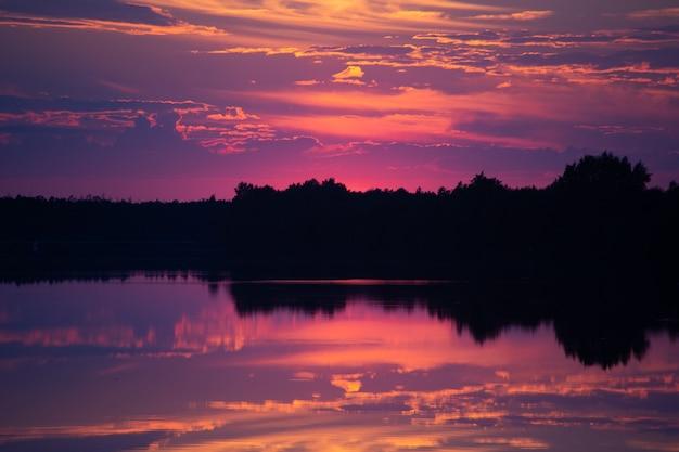 Zachód słońca i jego odbicie na powierzchni wody rzeki. jasne kolory i sylwetki drzew na brzegu.