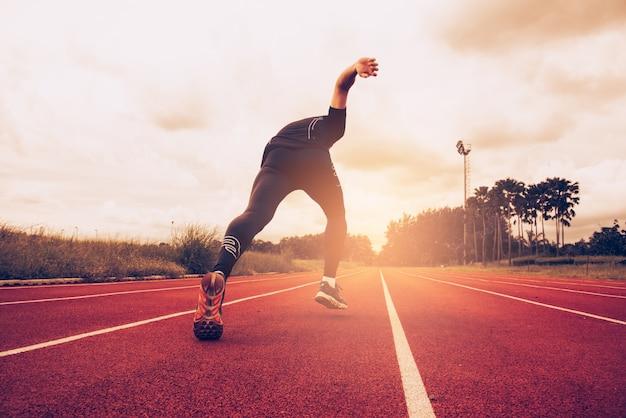 Zachód słońca i młody człowiek działa na pasie. sukces i cel koncepcji biznesowej
