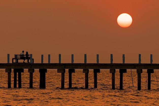 Zachód słońca i most na środku morza z kochankami