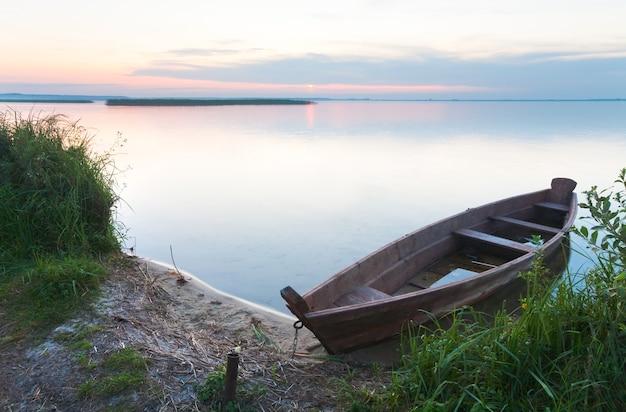 Zachód słońca i stara drewniana łódź powodziowa w pobliżu letniego brzegu jeziora (świtiaź, ukraina)