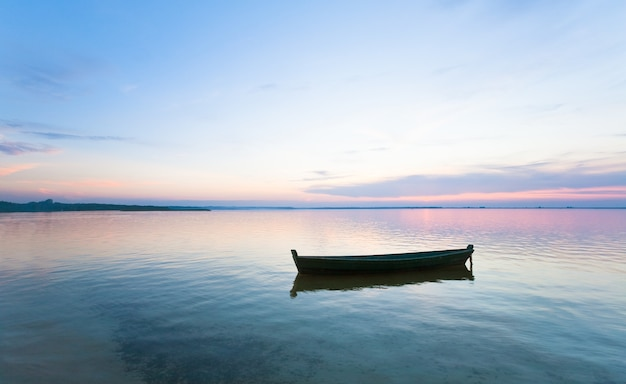 Zachód słońca i stara drewniana łódź rybacka na letnim brzegu jeziora (świtiaź, ukraina)