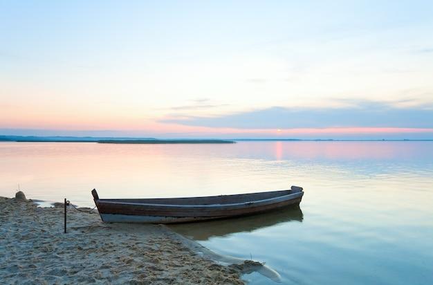 Zachód słońca i stara drewniana łódź rybacka w pobliżu letniego brzegu jeziora (świtiaź, ukraina)