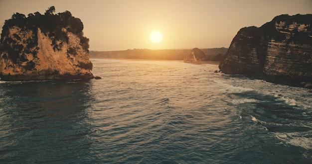Zachód słońca na brzegu skały z falami na seascape
