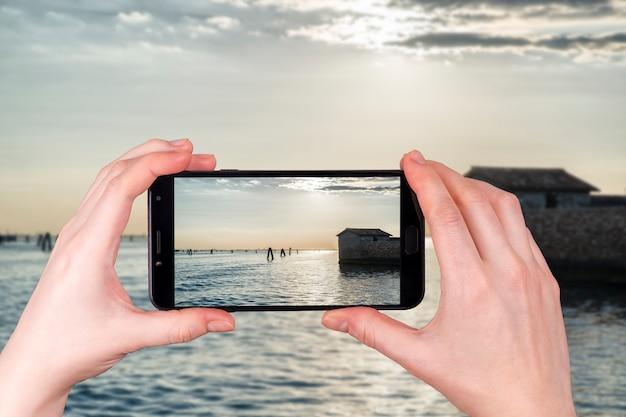 Zachód słońca na lagunie w wenecji we włoszech w letni wieczór. turysta robi zdjęcie