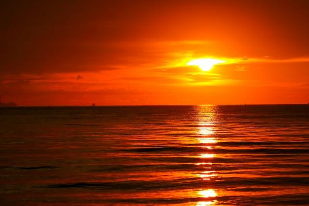 Zachód słońca na morzu i oceanie ostatnie światło czerwone niebo sylwetka chmury