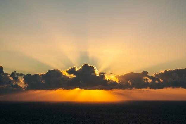 Zachód słońca na morzu i widzenie promieni słonecznych przez chmury