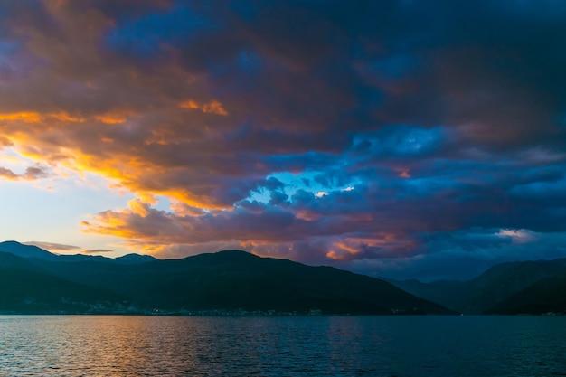 Zachód słońca na niebie czarnogóry nad wysokimi górami.