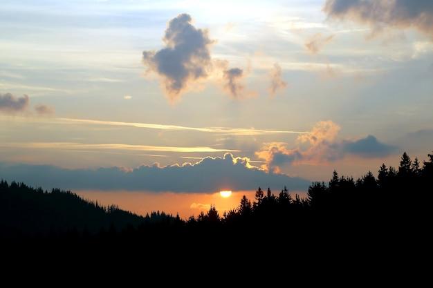Zachód słońca na niebie nad górami