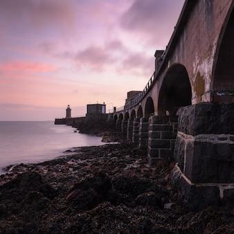Zachód słońca na niebie nad mostem i latarnią morską nad morzem na guernsey