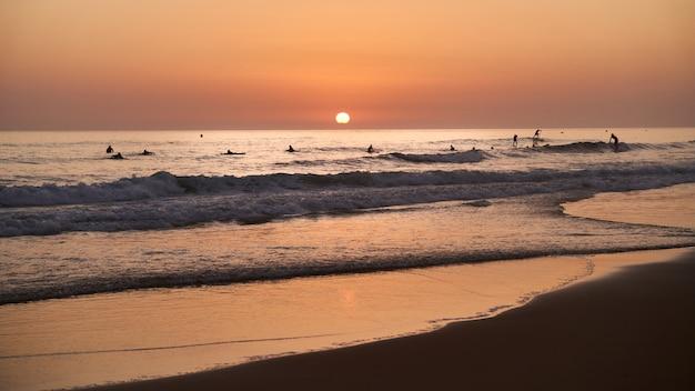 Zachód słońca na plaży z surferami w wodzie