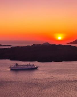 Zachód słońca na santorini, grecja i statek wycieczkowy na morzu,
