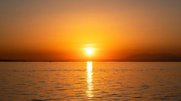 Zachód słońca na wybrzeżu morza egejskiego, statek i ląd w oddali, woda, grecja