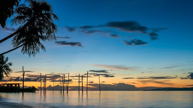 Zachód słońca na wyspie kri. łodzie pod palmami. raja ampat, indonezja, papua zachodnia