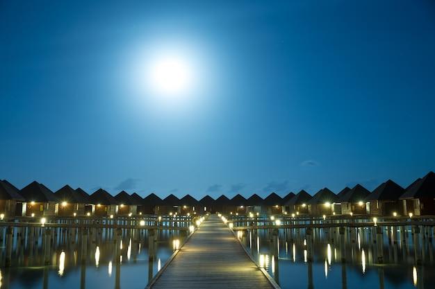 Zachód słońca na wyspie malediwy, kurort luksusowych willi na wodzie i drewniane molo.