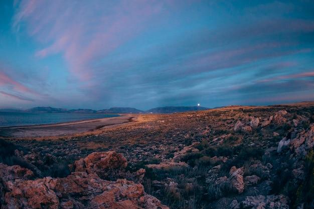 Zachód słońca na wzgórzach w pobliżu jeziora kamienie skały doliny księżyca