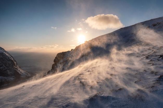 Zachód słońca na zaśnieżonym wzgórzu w zamieci o zachodzie słońca na górze ryten